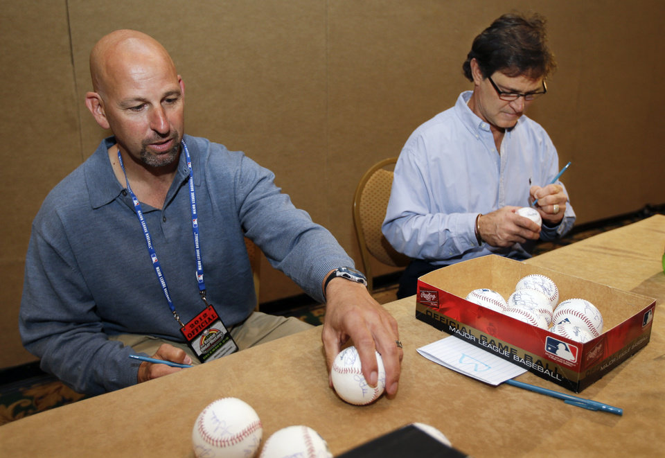 Photo - Colorado Rockies manager Walt Weiss, left, and Los Angeles Dodgers manager Don Mattingly, right, autograph baseballs at baseball's winter meetings on Tuesday, Dec. 4, 2012, in Nashville, Tenn. (AP Photo/Mark Humphrey)