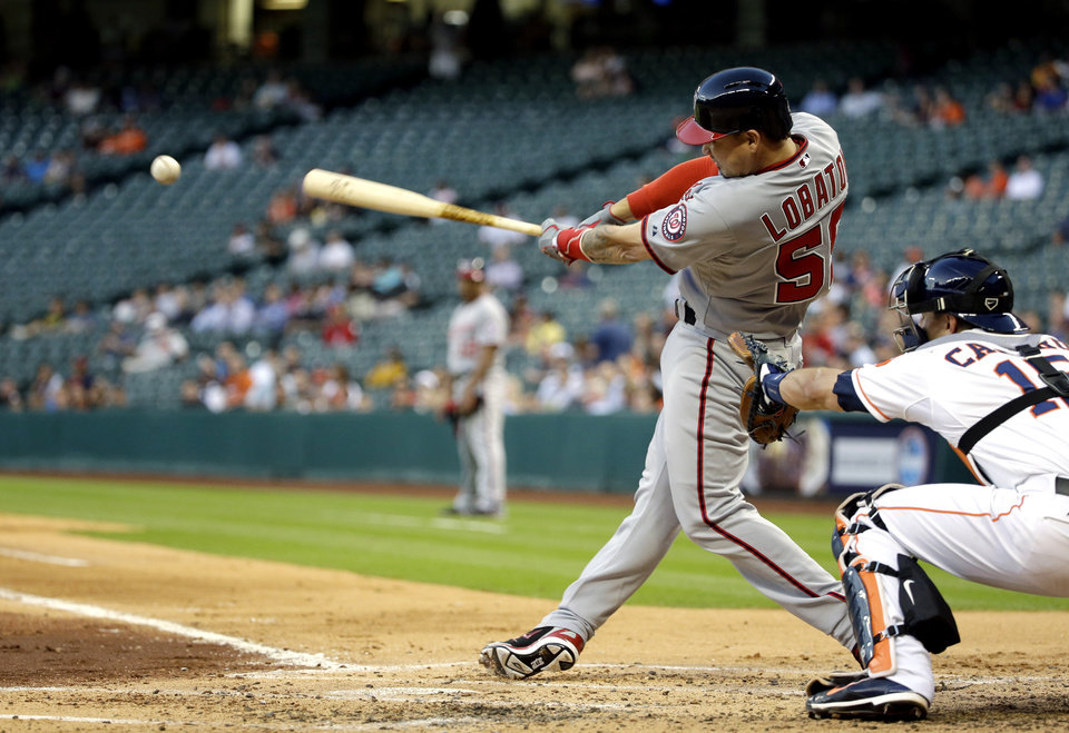 Photo - Washington Nationals' Jose Lobaton (59) hits a double that scored Kevin Frandsen during the third inning of a baseball game, as Houston Astros catcher Jason Castro (15) reaches for the pitch Tuesday, April 29, 2014, in Houston. (AP Photo/David J. Phillip)
