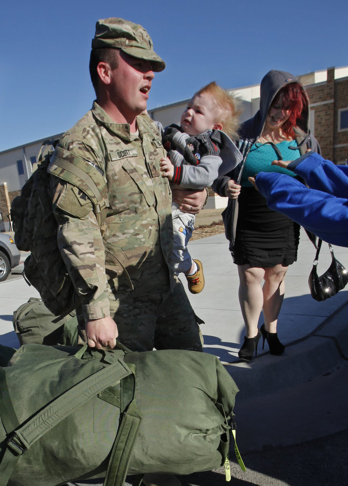 Spc. Galen Scott carries his six-month-old son Benjamin after a ceremony where he and other members of the Oklahoma National Guard were greeted by family and friends after returning from Afghanistan on Thursday, Jan. 12, 2012, in Norman, Okla.  His wife Jennifer is at right.