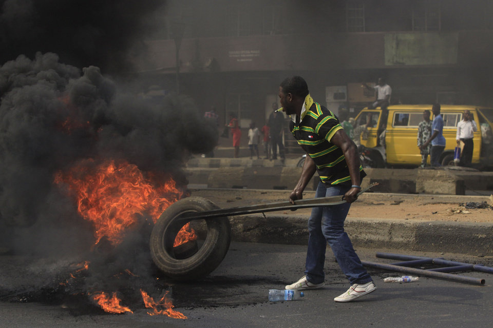Photo - FILE- An Unidentified man stocks the fire of a road block in the commercial capital of Lagos, Nigeria, during a fuel subsidy protest in this file photo dated Tuesday, Jan. 3, 2012, as angry mobs call on the government to keep a cherished consumer subsidy that had kept gas affordable for more than two decades. A 30-minute film documentary called