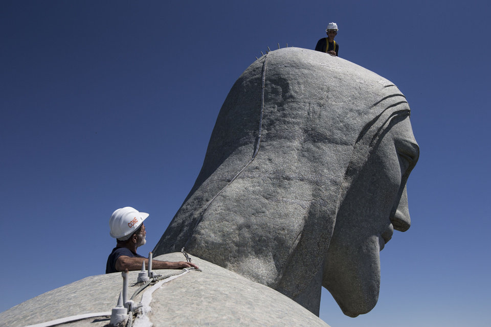 Photo - Repair workers examine the Christ Redeemer statue in Rio de Janeiro, Brazil, Tuesday, Jan. 21, 2014. The famed statue is being examined after two fingers and the head were chipped during recent lightning storms. Officials say they'll place more lightning rods on the statue in an effort to prevent future damage. (AP Photo/Felipe Dana)