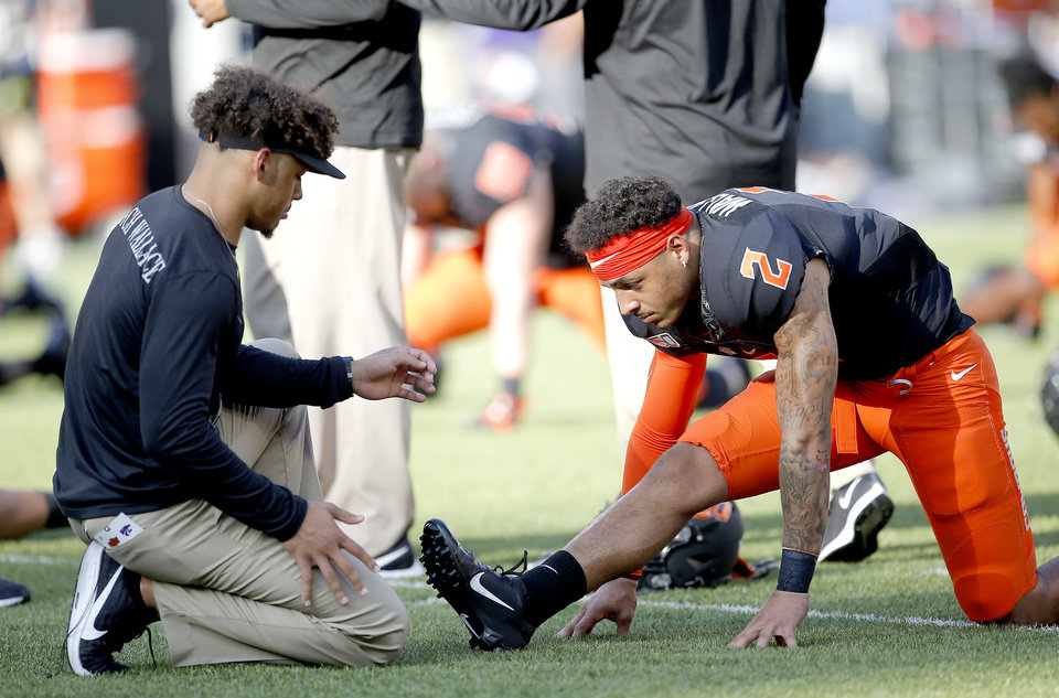 Photo - Tracin Wallaces stretches with his brotherOklahoma State's Tylan Wallace (2) before the college football game between the Oklahoma State Cowboys and the Kansas State Wildcats at Boone Pickens Stadium in Stillwater, Okla., Friday, Sept. 27, 2019. [Sarah Phipps/The Oklahoman]
