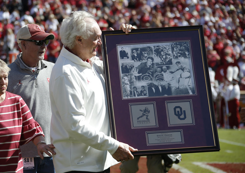 Photo - Steve Owens receives a plaque honoring him on the 50th anniversary of his Heisman Trophy during halftime of a college football game between the University of Oklahoma Sooners (OU) and the West Virginia Mountaineers at Gaylord Family-Oklahoma Memorial Stadium in Norman, Okla, Saturday, Oct. 19, 2019. Oklahoma won 52-14. [Bryan Terry/The Oklahoman]