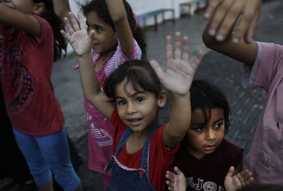 Photo - A displaced Palestinian girl participates in a play session with other children, at a U.N. school where they had sought refuge along with their families during the war, in Gaza City, Gaza Strip, Thursday, Aug. 7, 2014. Taking advantage of the continuing ceasefire, volunteers from the local non-profit NGO 'Tomooh' (Ambition), arranged a special play session for children to try and lessen the stress they've been enduring after the weeks of conflict. In the playground the children got a chance to sing and play group games under the caring eye of volunteers. They hope that their efforts will lessen the damage of the traumatic recent weeks events, or at least help them forget for a short while. (AP Photo/Lefteris Pitarakis)