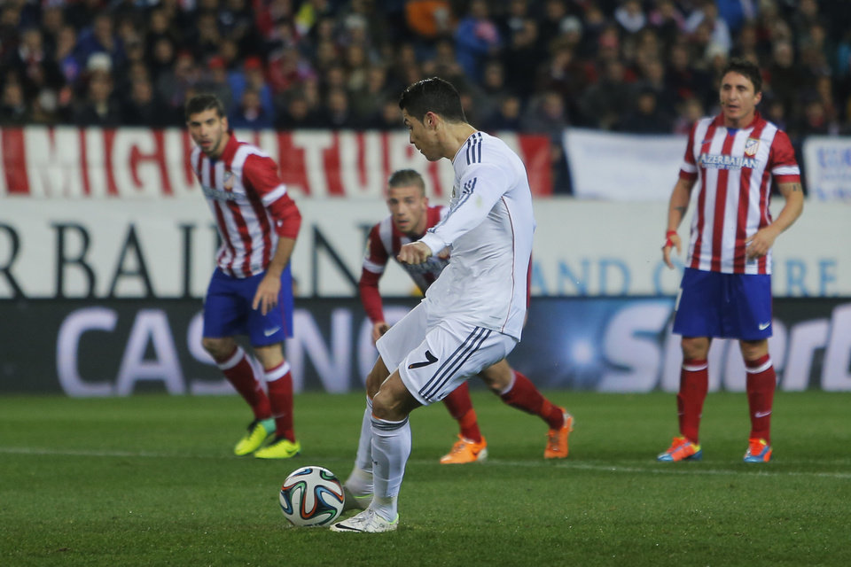 Photo - Real's Cristiano Ronaldo scores his goal during a semi final, 2nd leg, Copa del Rey soccer match between Atletico de Madrid and Real Madrid at the Vicente Calderon stadium in Madrid, Spain, Tuesday, Feb. 11, 2014. (AP Photo/Andres Kudacki)