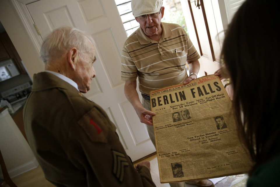 Photo - Korean war veteran John Rehage, center, show war memorabilia to his neighbor, eighty-nine-year-old Roland Chaisson, left, who stormed Normandy on D-Day when Germans killed half his squad before they could reach shore, pose for photographs in his home in Metairie, La., Wednesday, June 4, 2014. Chaisson is among D-Day veterans who will describe that day Friday and Saturday at the National World War II Museum. More than 15 hours of observances are planned Friday, the invasion's 70th anniversary. (AP Photo/Gerald Herbert)