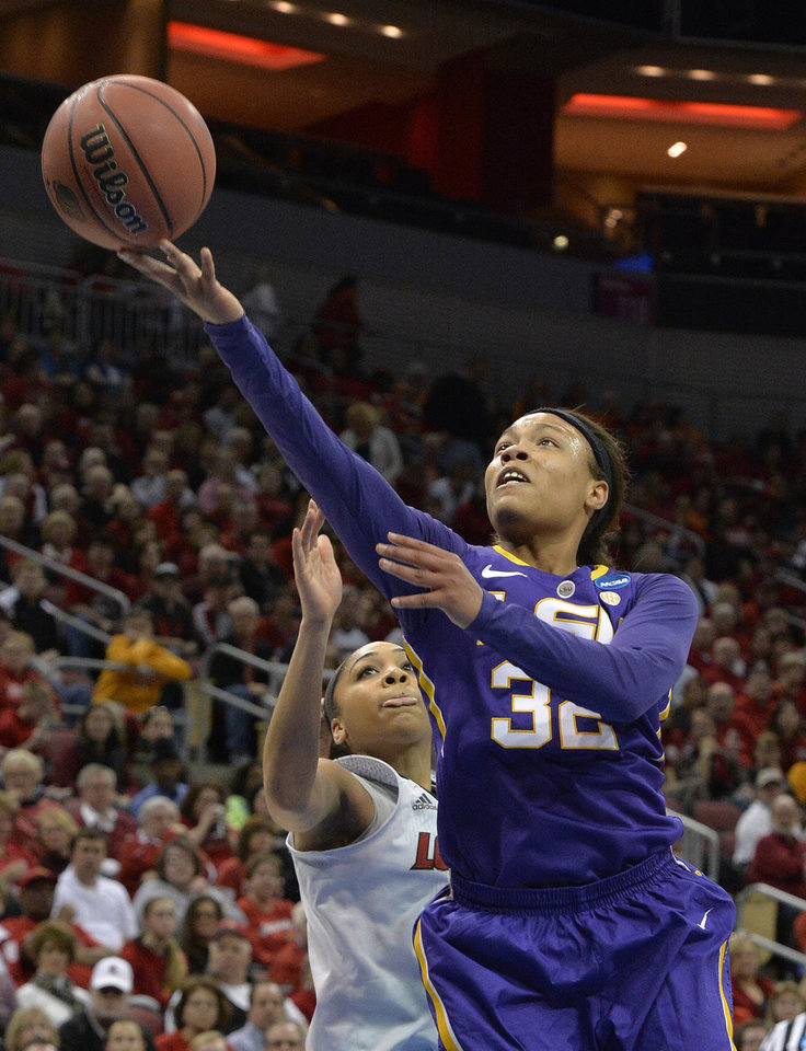 Photo - LSU's Danielle Ballard, right, shoots past the defense of Louisville's Bria Smith during the first half in a regional semifinal game at the NCAA women's college basketball tournament on Sunday, March 30, 2014, in Louisville, Ky. (AP Photo/Timothy D. Easley)