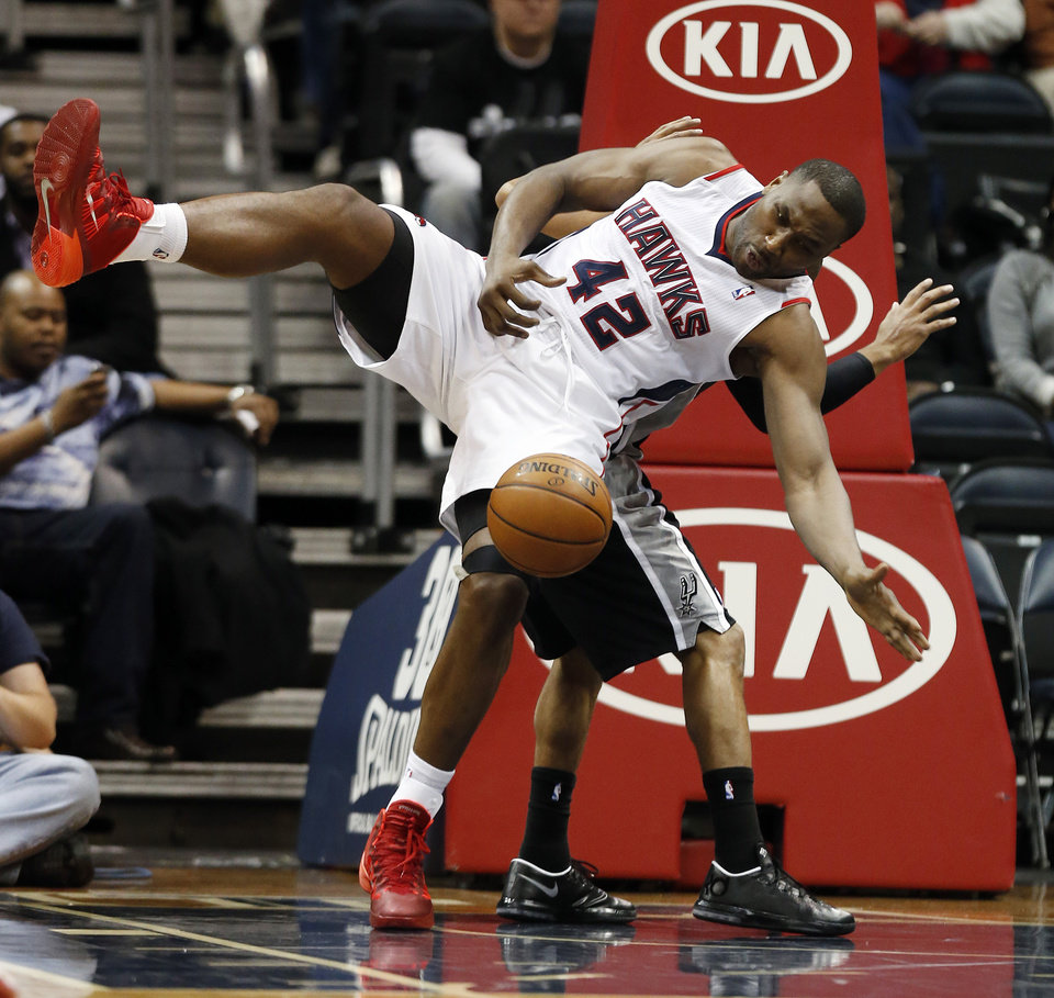 Photo - Atlanta Hawks power forward Elton Brand (42) reaches for a rebound against the San Antonio Spurs in the first half of an NBA basketball game Friday, Jan. 24, 2014, in Atlanta.  (AP Photo/John Bazemore)