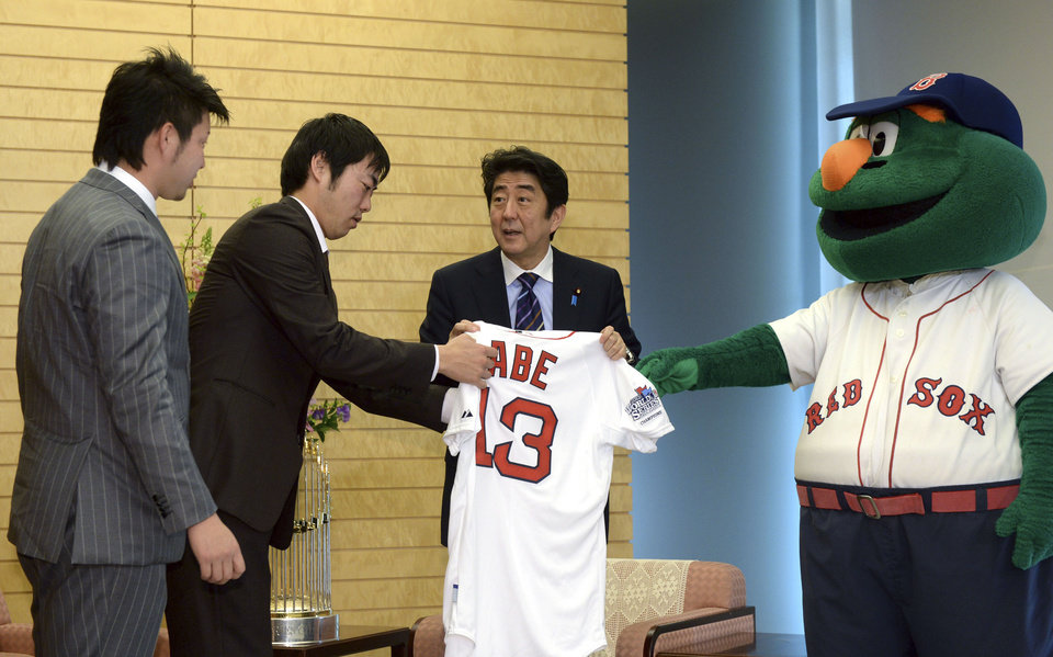 Photo - Japanese Prime Minister Shinzo Abe, second right, is presented a Boston Red Sox uniform from Japanese pitchers of the World Series champion team, Koji Uehara, second left, and Junichi Tazawa, left, and the team's mascot Wally the Green Monster at his official residence in Tokyo Tuesday, Jan. 21, 2014. The two Japanese major leaguers who brought the MLB's World Series trophy, seen on the desk, bottom left, to Japan visited Abe shortly before unveiling it to the public. (AP Photo/Yoshikazu Tsuno, Pool)