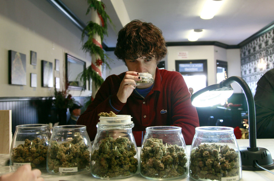 File - In this Dec. 15, 2011 file photo, medical marijuana patient Kevin Brown smells marijuana available at The Apothecarium Medical Cannabis Dispensary in San Francisco. California cities and counties can ban  medical marijuana dispensaries, the state's highest court ruled Monday in a unanimous opinion likely to further diminish California's once-robust medical marijuana industry. The California Supreme Court said neither the state's voter-approved law legalizing medical marijuana nor a companion measure adopted by the Legislature prevent local governments from using their land use and zoning powers to prohibit storefront dispensaries. (AP Photo/Jeff Chiu, file)