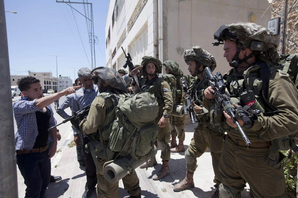 Photo - A Palestinian youth argues with Israeli soldiers as he tries to enter his home during a military operation to search for three missing teenagers outside the West Bank city of Hebron, Sunday, June 15, 2014. Israeli troops on Sunday arrested some 80 Palestinians, including dozens of members of Hamas, in an overnight raid in the West Bank as Prime Minister Benjamin Netanyahu accused the Islamic militant group of kidnapping three teenagers who went missing nearly three days ago. (AP Photo/Majdi Mohammed)