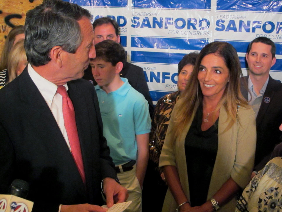 Photo - Former South Carolina Gov. Mark Sanford thanks his fiance Maria Belen Chapur as he addresses supporters in Mount Pleasant, S.C., on Tuesday, April 2, 2013, after winning the GOP nomination for the U.S. House seat he once held. Sanford is trying to make a comeback after his political career was derailed four years ago when he disappeared from the state only to return to admit the couple was having an affair. Sanford's wife, Jenny, later divorced him. (AP Photo/Bruce Smith)