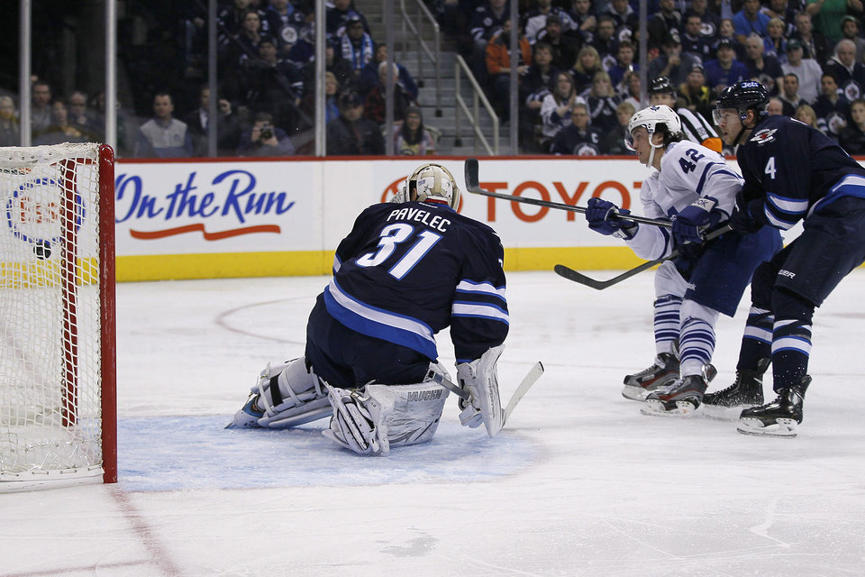 Toronto Maple Leafs' Tyler Bozak (42) scores on Winnipeg Jets goaltender Ondrej Pavelec (31) and Paul Postma (4) during second period NHL action in Winnipeg on Thursday, Feb. 7, 2013. (AP Photo/The Canadian Press, John Woods)
