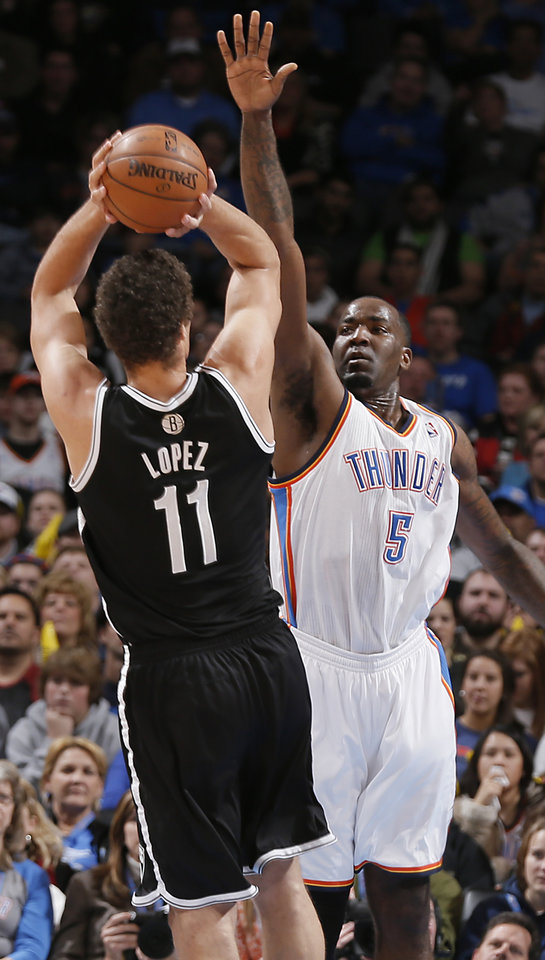 Photo - Oklahoma City's Kendrick Perkins (5) defends on Brooklyn Nets' Brook Lopez (11) during the NBA basketball game between the Oklahoma City Thunder and the Brooklyn Nets at the Chesapeake Energy Arena on Wednesday, Jan. 2, 2013, in Oklahoma City, Okla. Photo by Chris Landsberger, The Oklahoman