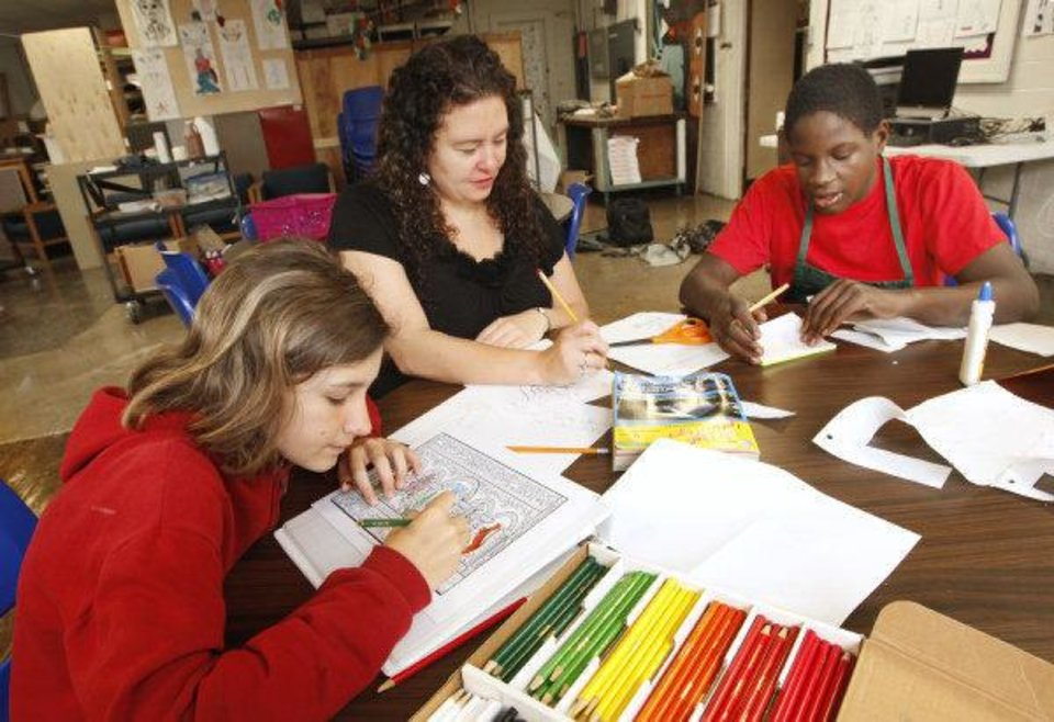 Photo - Seventh-grader Karley Carter, 12,  church volunteer Lechelle Calderwood, and seventh-grader Quintin Hammons, 13, work on art projects durng the