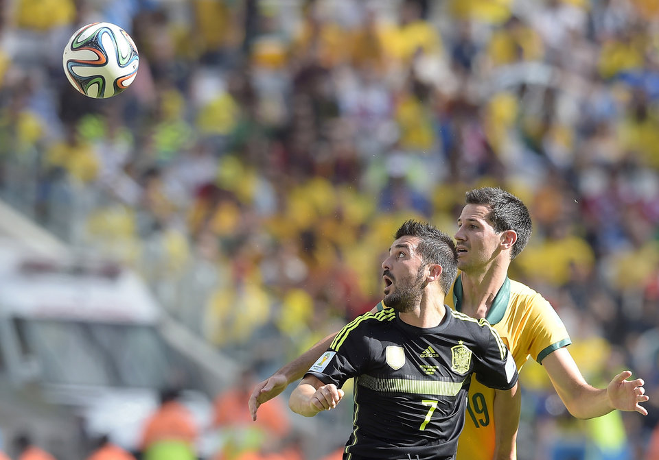Photo - Spain's David Villa, left, and Australia's Ryan McGowan go for a header during the group B World Cup soccer match between Australia and Spain at the Arena da Baixada in Curitiba, Brazil, Monday, June 23, 2014. (AP Photo/Manu Fernandez)