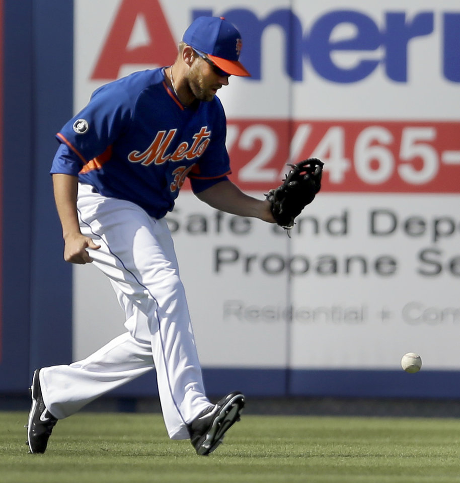 Photo - New York Mets left fielder Andrew Brown drops a ball hit by St. Louis Cardinals' Jon Jay during the sixth inning of an exhibition spring training baseball game Friday, March 7, 2014, in Port St. Lucie, Fla. Jay ended up at second and Brown was charged with an error on the play. (AP Photo/Jeff Roberson)