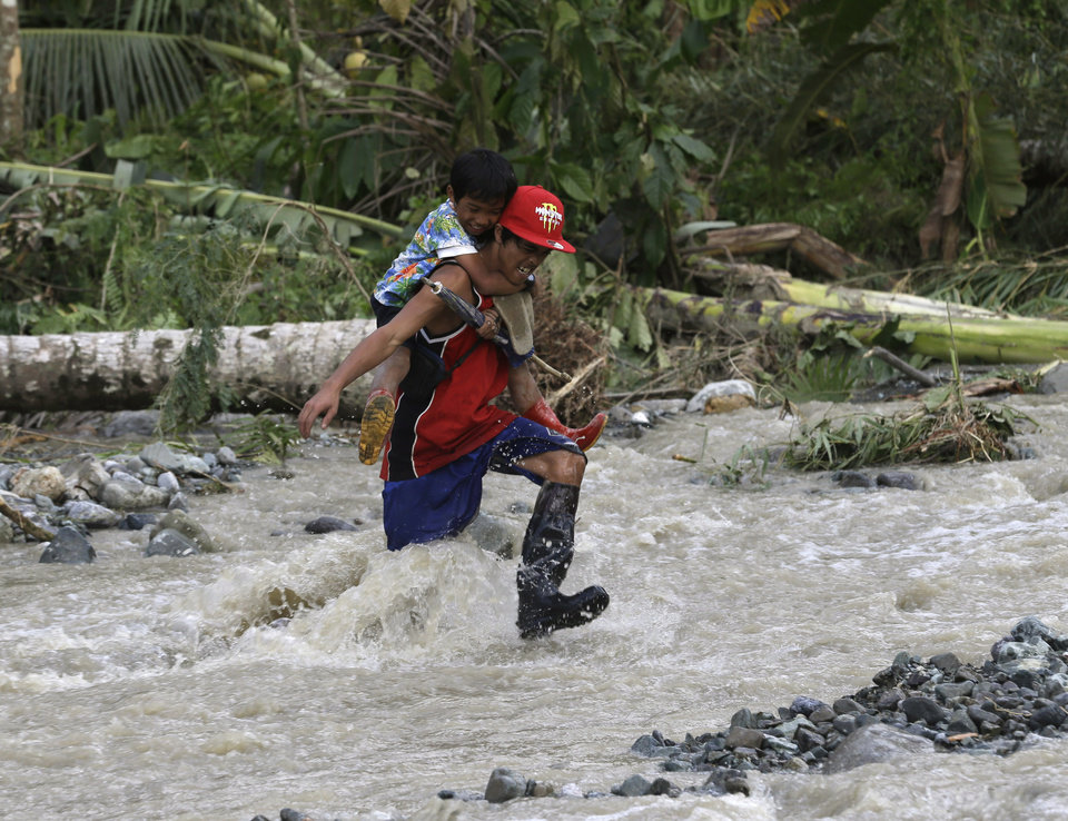 Residents cross a river in the flash flood-hit village of Andap, a day after Typhoon Bopha made landfall, in New Bataan township, Compostela Valley in southern Philippines Wednesday Dec. 5, 2012.  Typhoon Bopha, one of the strongest typhoons to hit the Philippines this year, barreled across the country's south on Tuesday, killing scores of people while triggering landslides, flooding and cutting off power in two entire provinces. (AP Photo/Bullit Marquez)