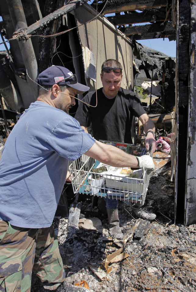 Photo - Mike Arata, left, takes a basket of items from Todd Sewell that managed to survive the fire that destroyed Sewell's home at 11533 Berkshire Ct. in Midwest City, Okla., Saturday, April 11, 2009. Wildfires struck the area on Thursday, April 9, 2009, destroying several homes. Arata is a co-worker of Sewell who was helping him look for items that could be recovered. Photo by Nate Billings, The Oklahoman