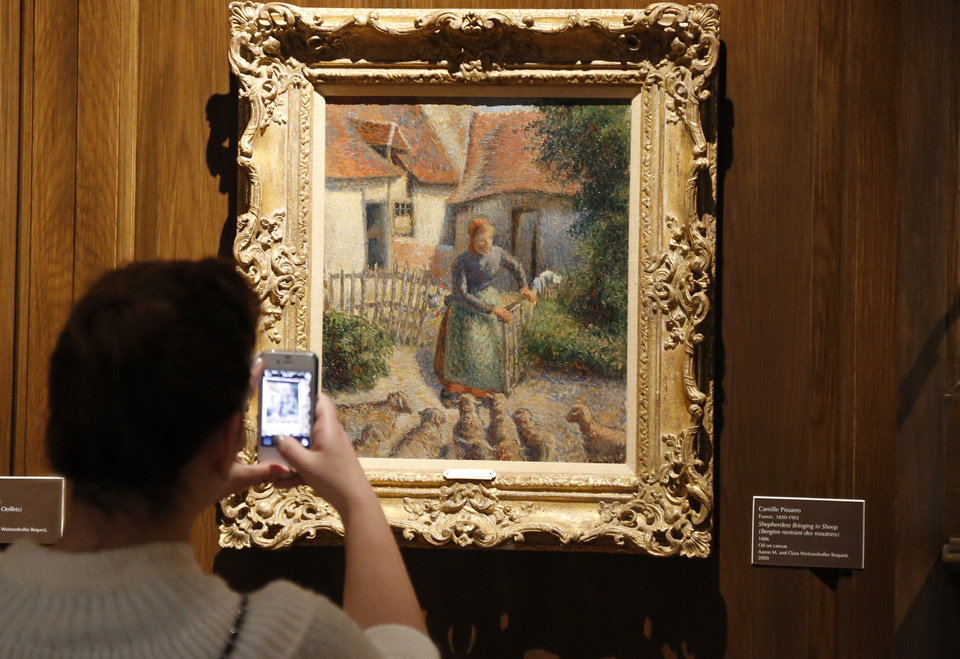 "Photo - In a Saturday, Feb. 8, 2014 photo, a visitor to the Fred Jones Jr. Museum of Art at the University of Oklahoma in Norman, Okla., takes a photograph of a piece called ""Shepherdess Bringing in Sheep"" by French impressionist artist Camille Pissarro at the museum. For more than a decade, the University of Oklahoma has exhibited  ""Shepherdess Bringing in Sheep,"" bequeathed to it by the wife of an oil tycoon. But renewed claims by a family that owned the oil painting before World War II has drawn the school's fundraising arm into a fight it thought was settled in Switzerland more than 60 years ago.  (AP Photo/Sue Ogrocki)"
