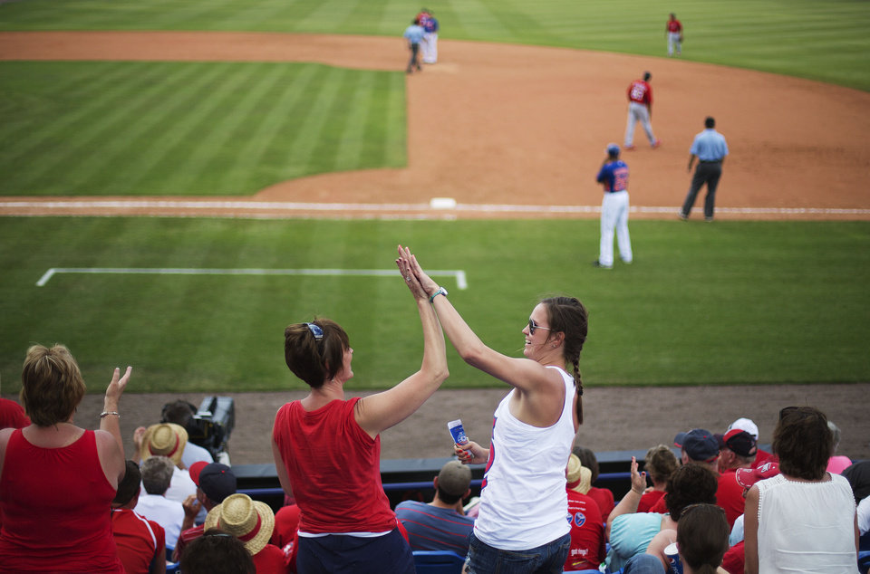Photo - St. Louis Cardinals fans high-five one another after New York Mets' Brandon Allen grounded out putting the Cardinals one out away from beating the Mets in the ninth inning of an exhibition spring training baseball game, Wednesday, March 12, 2014, in Port St. Lucie, Fla. (AP Photo/David Goldman)