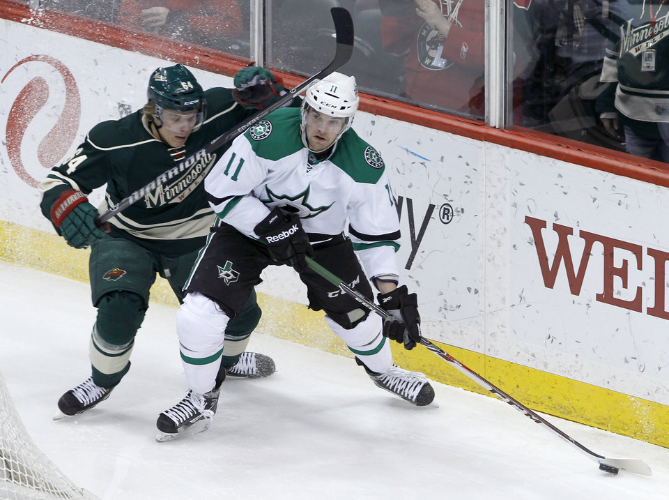 Photo - Dallas Stars center Dustin Jeffrey (11) controls the puck in front of Minnesota Wild center Mikael Granlund, left, of Finland, during the first period of an NHL hockey game in St. Paul, Minn., Saturday, Jan. 18, 2014. (AP Photo/Ann Heisenfelt)