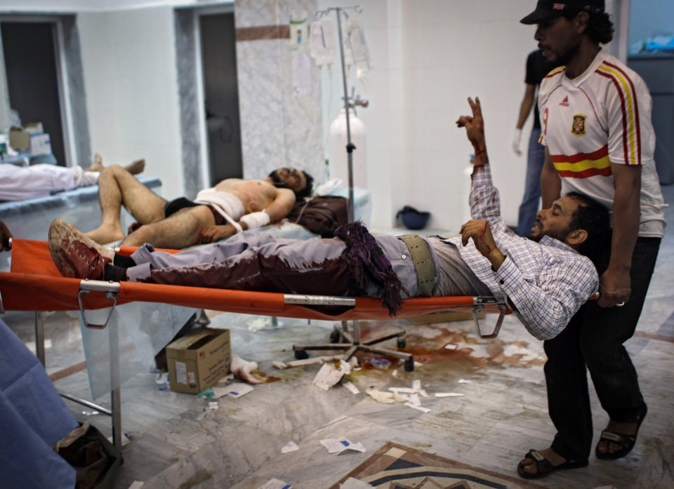 Volunteers carry a wounded rebel fighter in the Abu-Rafat hospital on the outskirts of Zawiya, LIbya, Sunday, Aug. 21, 2011. Libyan rebels said they were less than 20 miles (30 kilometers) from Moammar Gadhafi's main stronghold of Tripoli on Sunday, a day after opposition fighters launched their first attack on the capital itself. Fighters said a 600-strong rebel force that set out from Zawiya has reached the outskirts of the village of Jedaim and was coming under heavy fire from regime forces on the eastern side of the town. (AP Photo/Sergey Ponomarev)