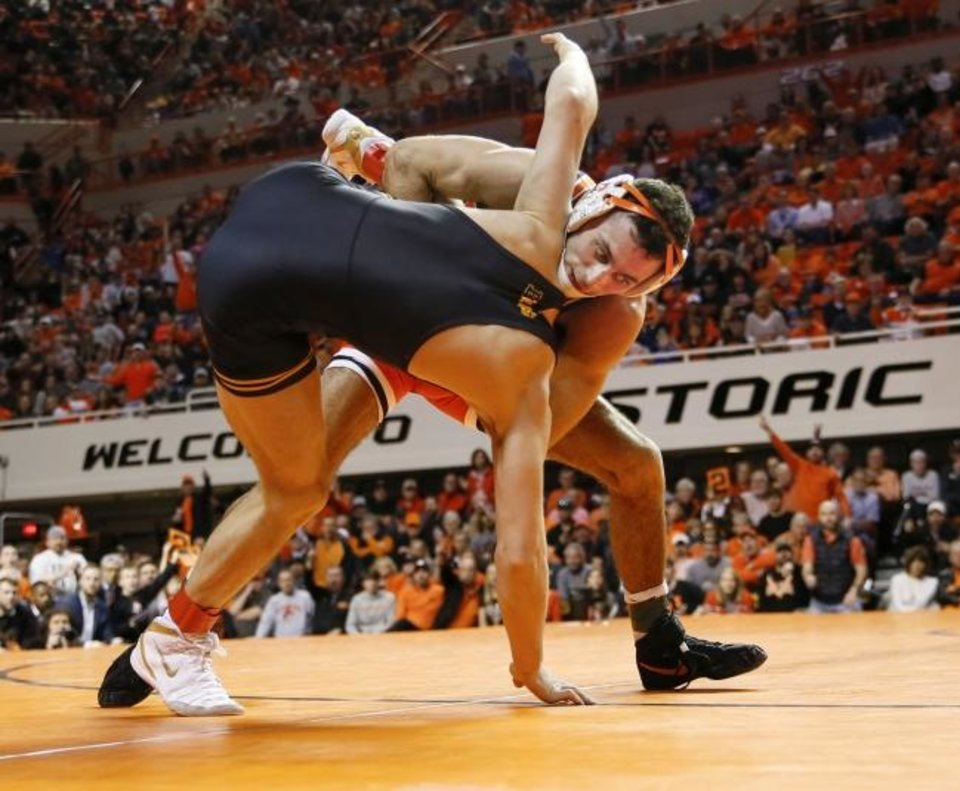 Photo -  OSU's Nick Piccininni, back, wrestles Iowa's Spencer Lee in a 125-pound match during Sunday's dual between college powerhouses. Piccininni ended up pinning Lee to help the Cowboys take a 27-12 victory before a sold out crowd at Gallagher-Iba Arena. [Nate Billings, The Oklahoman]
