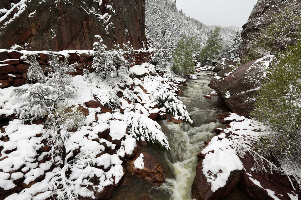 Photo - Water flows down a canyon past fresh snow, at Eldorado Canyon State Park, in Eldorado Springs, Colo., on Monday, May 12, 2014. A spring storm has brought up to 3 feet of snow to the Rockies and severe thunderstorms and tornadoes to the Midwest. In Colorado, the snow that began falling on Mother's Day caused some power outages as it weighed down newly greening trees. (AP Photo/Brennan Linsley)