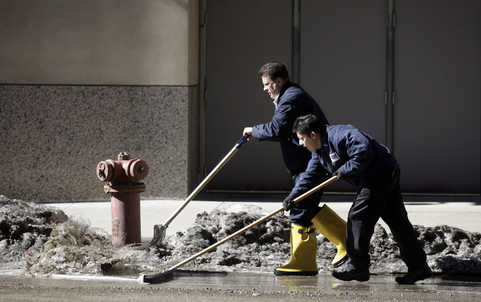 Photo - Workers at a downtown parking garage removes snow melt water to the storm drain Wednesday, Feb. 19, 2014, in Chicago. Weeks of subfreezing weather are giving way, at least briefly, to temperatures in the 50s, putting cities on guard for flooding, roof collapses and clogged storm drains. (AP Photo/Kiichiro Sato)