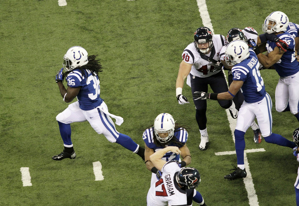 Photo - Indianapolis Colts' Deji Karim, left, runs back a kickoff 101-yards for a touchdown during the second half of an NFL football game against the Houston Texans Sunday, Dec. 30, 2012, in Indianapolis. (AP Photo/AJ Mast)