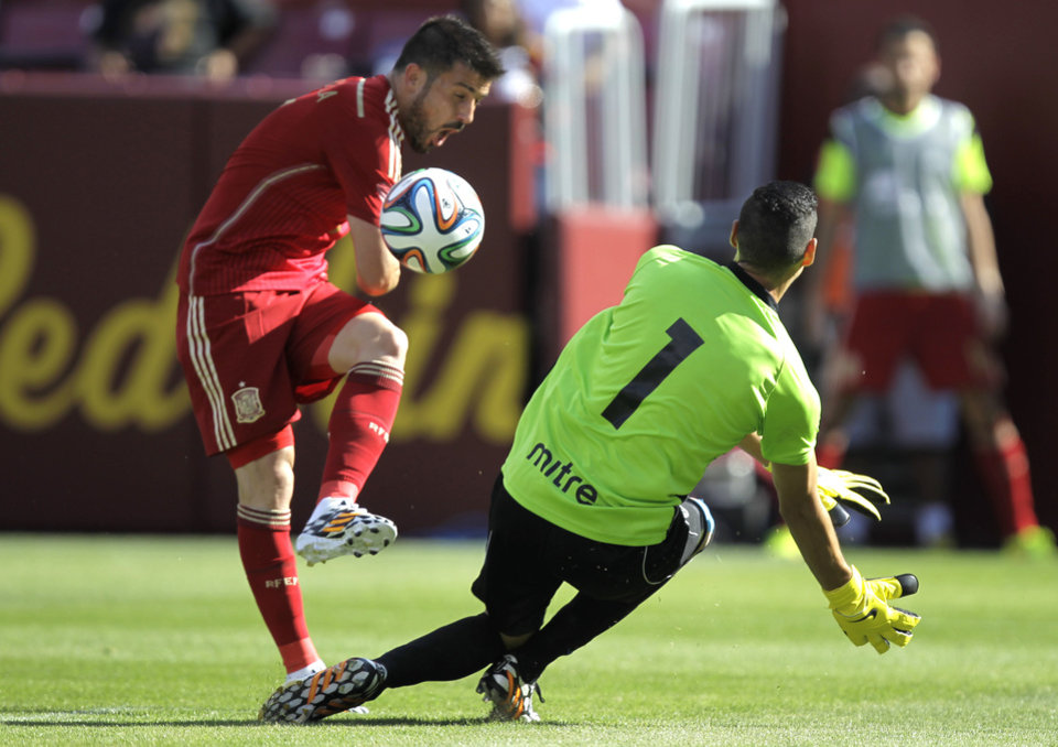 Photo - Spain's David Villa, left, kicks the ball as El Salvador goalkeeper  Derby Carrillo (1)  defends during the second half of an exhibition soccer game, Saturday, June 7, 2014, in Landover, Md. Spain won 2-0. (AP Photo/Luis M. Alvarez)
