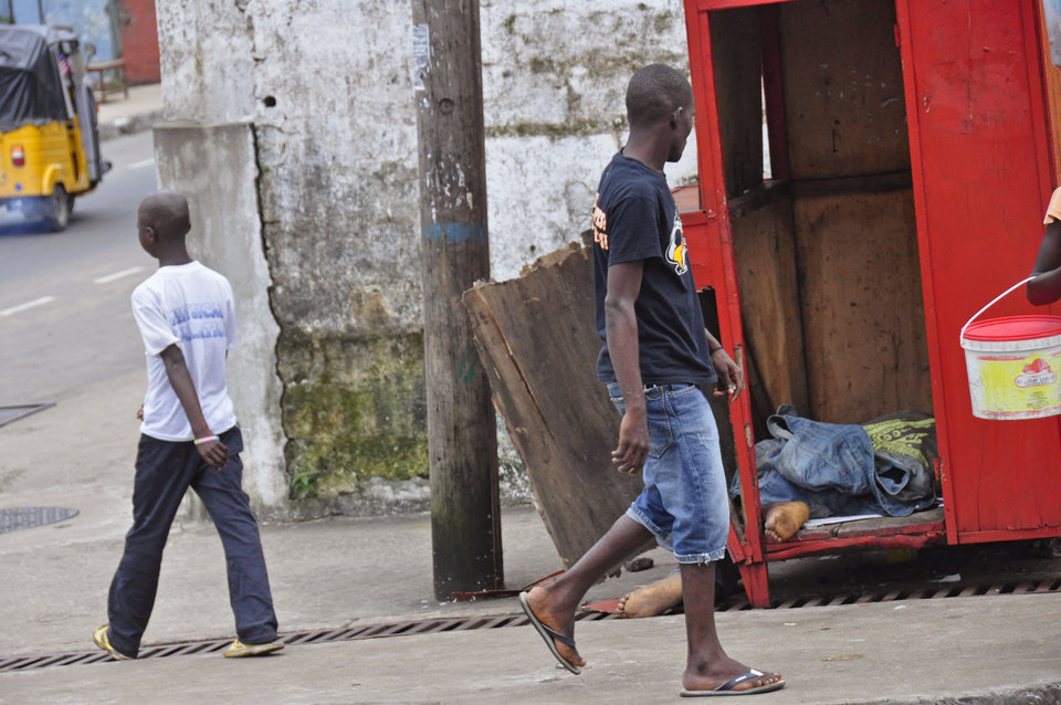 Photo - In this photo taken on Saturday, Aug. 16, 2014,  a man, center, looks at the body of another man, right, suspected of dying from the Ebola virus on one of the busiest streets  in Monrovia, Liberia. Liberian officials fear Ebola could soon spread through the capital's largest slum after residents raided a quarantine center for suspected patients and took items including blood-stained sheets and mattresses. The violence in the West Point slum occurred late Saturday and was led by residents angry that patients were brought from other parts of the capital to the holding center, Tolbert Nyenswah, assistant health minister, said Sunday. (AP Photo/Abbas Dulleh)