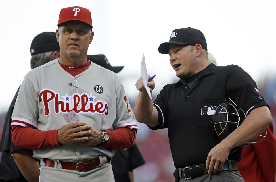 Photo - Philadelphia Phillies manager Ryne Sandberg, left, goes over the ground rules with home plate umpire Sean Barber prior to a baseball game against the Cincinnati Reds, Friday, June 6, 2014, in Cincinnati. (AP Photo/Al Behrman)