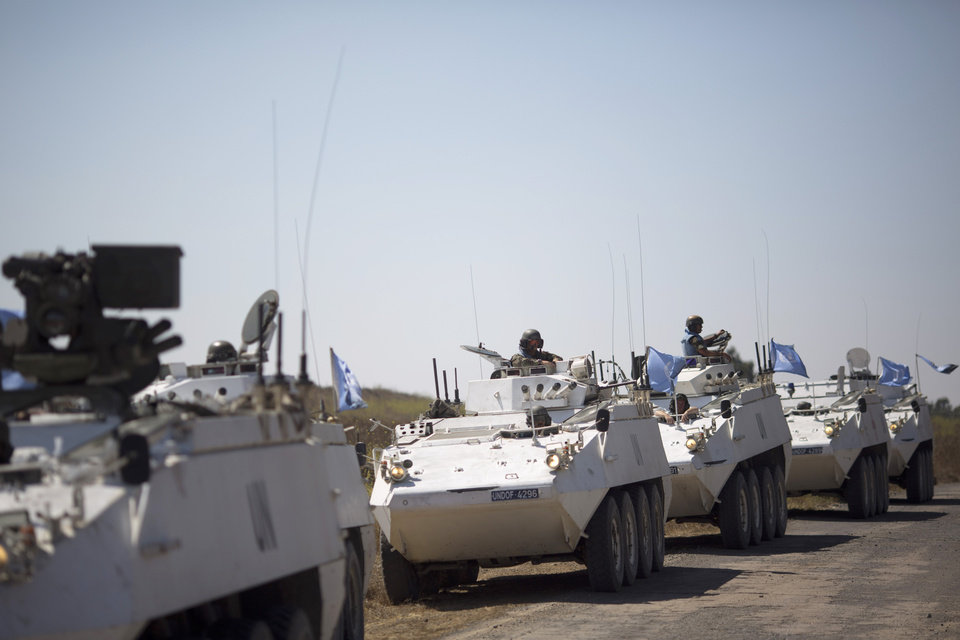Photo - Armored vehicles from the U.N. peacekeepers of the United Nations Disengagement Observer Force, also known as UNDOF wait to cross from the Israeli controlled Golan Heights to Syria, Thursday, Aug. 28, 2014.  In southern Syria,  government warplanes targeted rebels near the country's frontier with Israel in the Golan Heights, a day after opposition fighters captured a crossing point on the disputed border.  (AP Photo/Ariel Schalit)