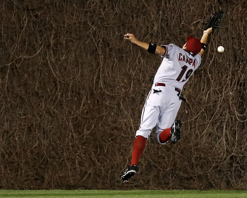 Photo - Arizona Diamondbacks center fielder Tony Campana misses the catch on an RBI double hit by the Chicago Cubs' Travis Wood during the fourth inning of a baseball game on Monday, April 21, 2014, in Chicago. (AP Photo/Andrew A. Nelles)