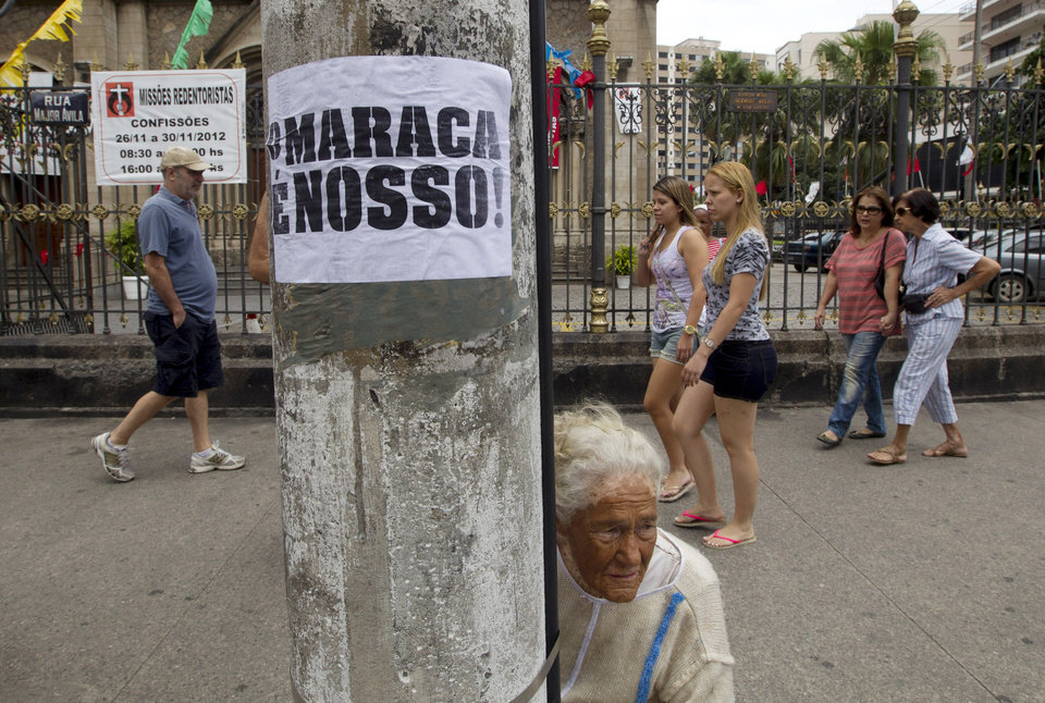 Photo - Pedestrians walk past a pole displaying a poster that reads in Portuguese;