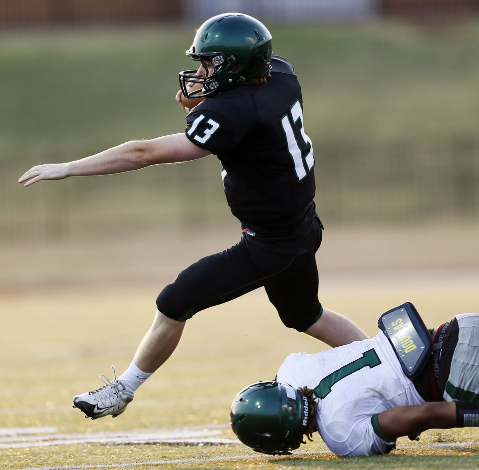 Norman North's Peyton Gavras (13) scrambles away from Edmond Santa Fe's Phillip Sumpter (1) during a high school football scrimmage at Moore Stadium between Edmond Santa Fe and Norman North in Moore, Okla., Thursday, Aug. 16, 2012. Photo by Nate Billings, The Oklahoman