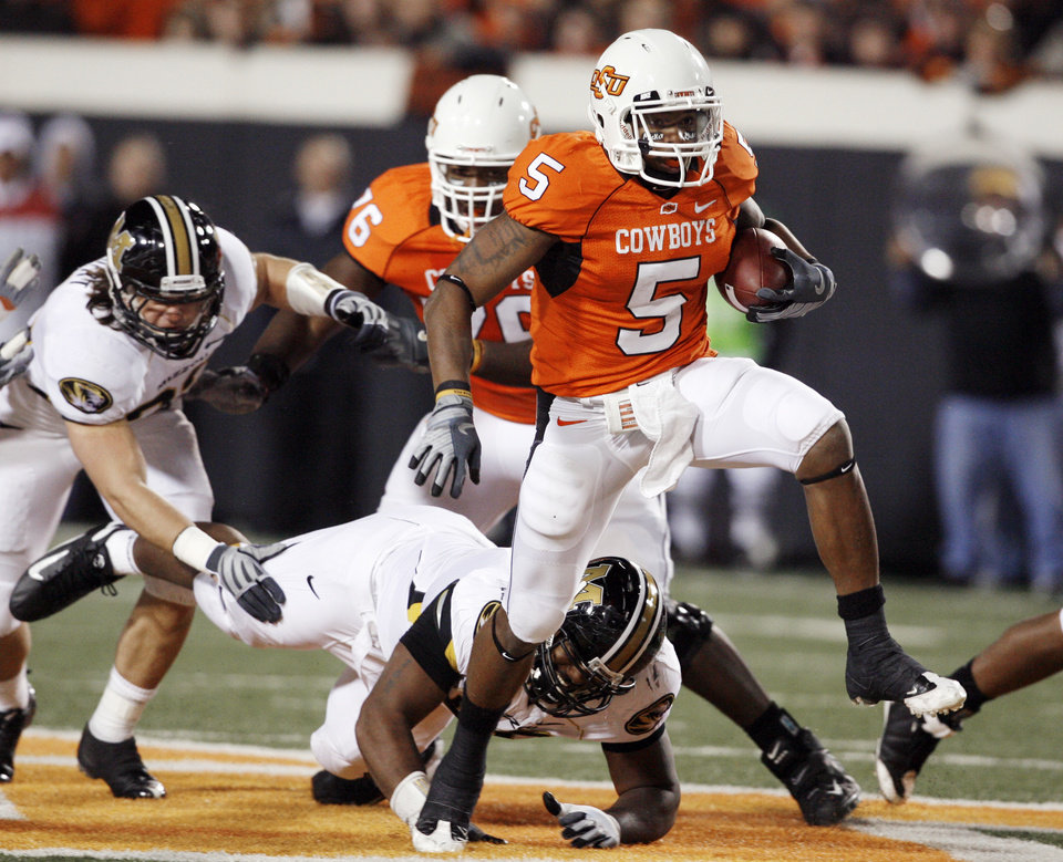 Photo - Keith Toston breaks a tackle during the first half of the college football game between Oklahoma State University (OSU) and the University of Missouri (MU) at Boone Pickens Stadium in Stillwater, Okla. Saturday, Oct. 17, 2009.  Photo by Steve Sisney, The Oklahoman