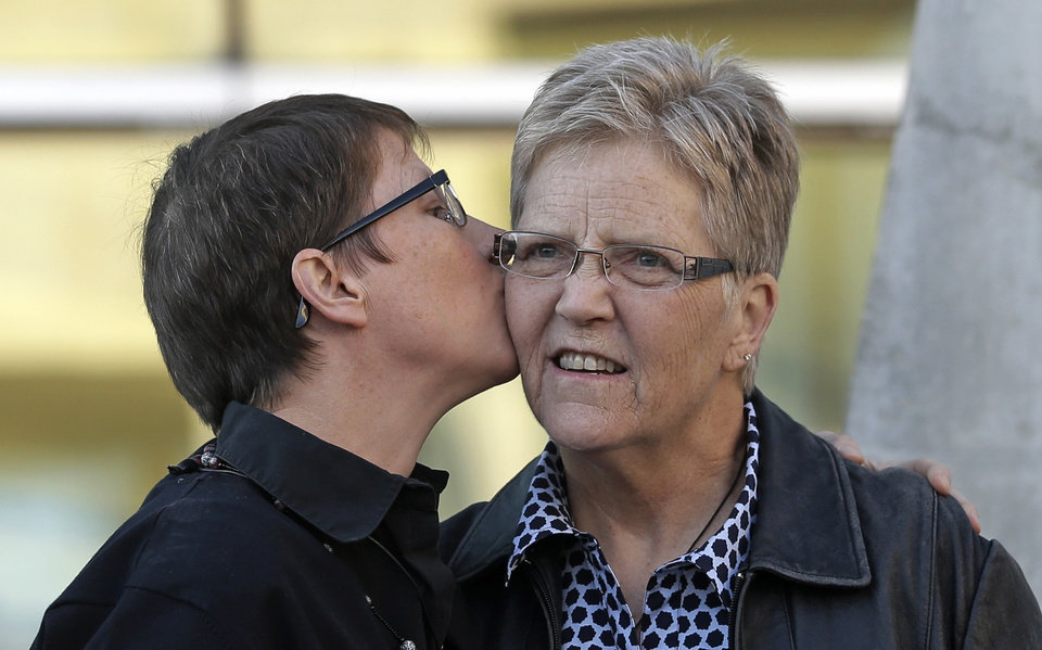 Photo - Kody Partridge, left, kisses Laurie Wood, right, at the Utah Unites for Marriage