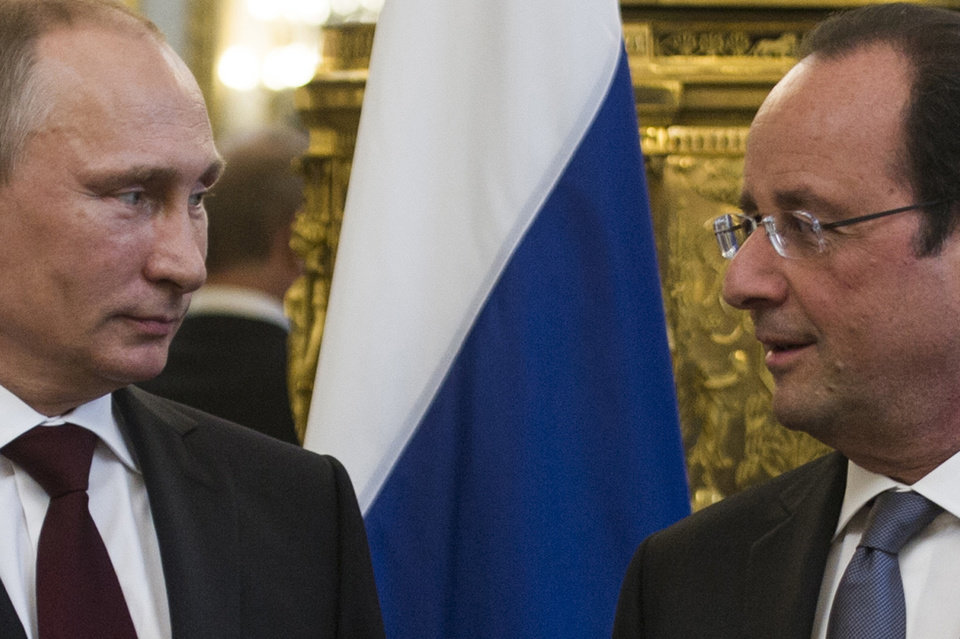 Photo - French President Francois Hollande, right, poses with Russian President Vladimir Putin prior to their meeting at the Elysee Palace in Paris, Thursday, June 5, 2014. Putin is in France with a host of world leaders for celebrations marking the 70th anniversary of the Normandy D-Day landings during World War II. (AP Photo/Fred Dufour, Pool)