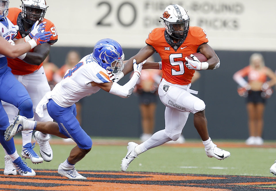 Photo - Oklahoma State's Justice Hill (5) gets by Boise State's DeAndre Pierce (4) in the third quarter during a college football game between the Oklahoma State Cowboys (OSU) and the Boise State Broncos at Boone Pickens Stadium in Stillwater, Okla., Saturday, Sept. 15, 2018. OSU won 44-21. Photo by Sarah Phipps, The Oklahoman