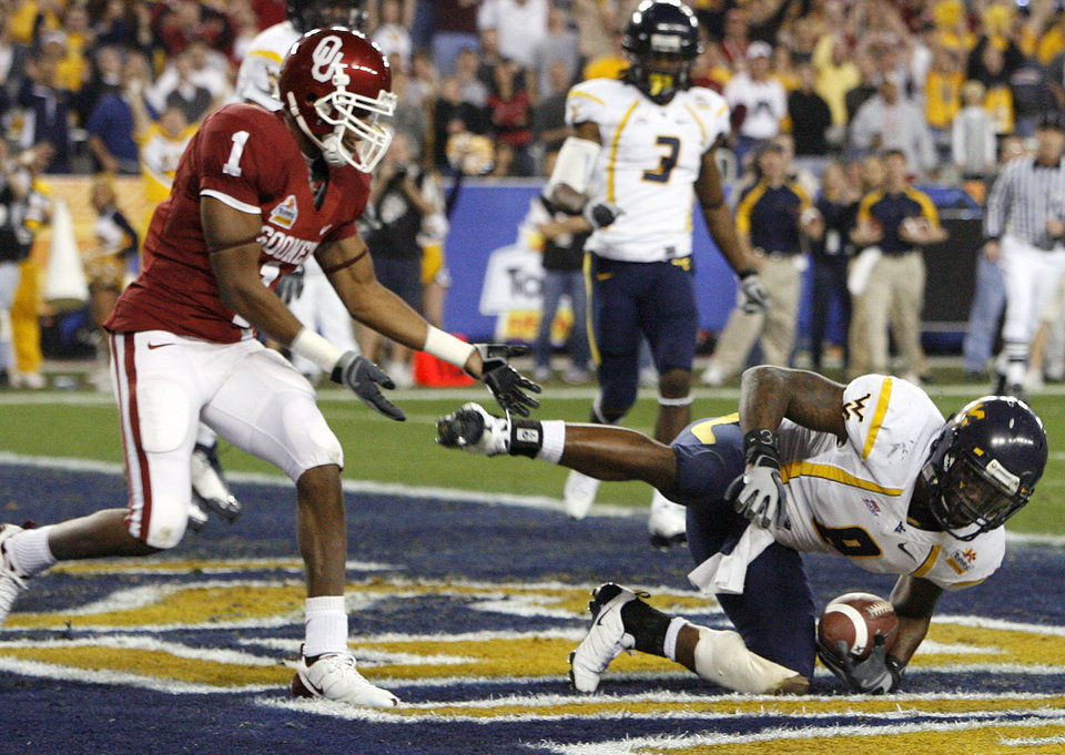 Photo - West Virginia's Quinton Andrews (8) intercepts a pass intended for Oklahoma's Manuel Johnson (1) in the endzone during the first half of the Fiesta Bowl college football game between the University of Oklahoma Sooners (OU) and the West Virginia University Mountaineers (WVU) at The University of Phoenix Stadium on Wednesday, Jan. 2, 2008, in Glendale, Ariz. 