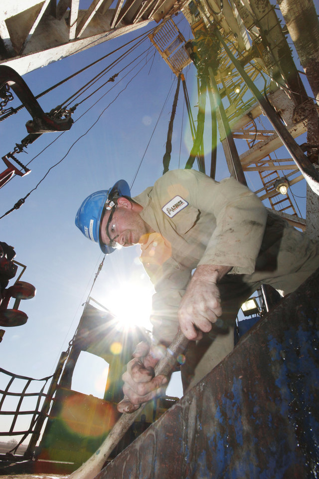 Photo - Floorman William Reed scrubs down the deck on the willing platform on a SandRidge oil drilling rig near Medford. Photo By David McDaniel, The Oklahoman  David McDaniel