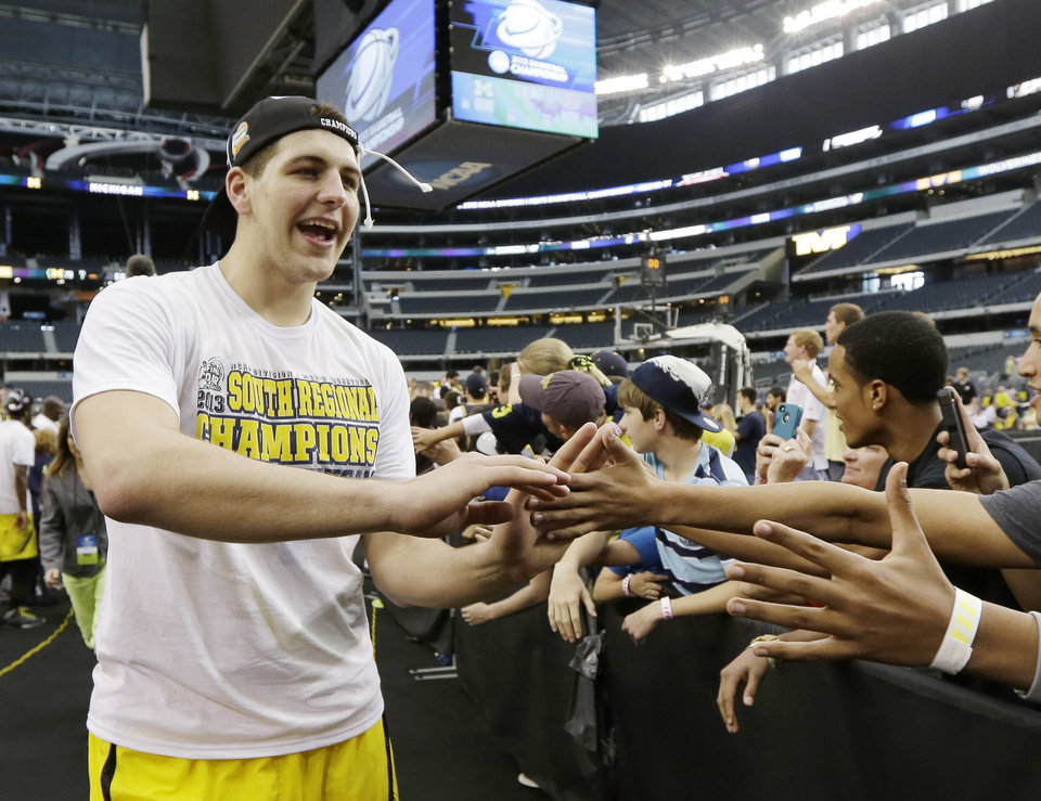 Photo - Michigan's Mitch McGary celebrates after a regional final game against Florida in the NCAA college basketball tournament, Sunday, March 31, 2013, in Arlington, Texas. Michigan won 79-59 to advance to the Final Four. (AP Photo/David J. Phillip)