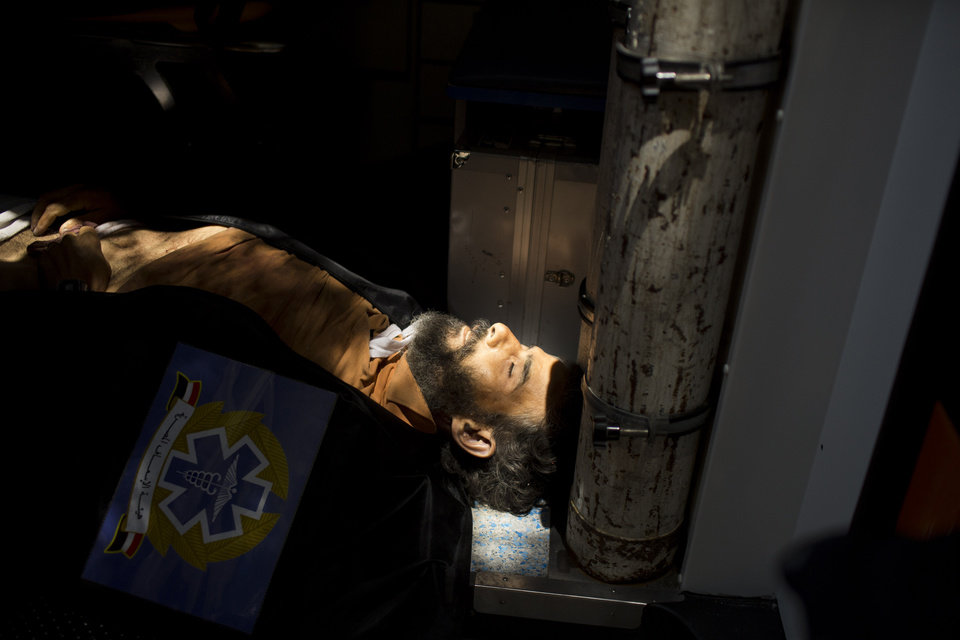 Photo - The body of a supporter for Egypt's ousted President Mohammed Morsi lies in an ambulance in Cairo, Egypt, Monday, July 8, 2013. Egyptian soldiers and police opened fire on supporters of the ousted president early Monday in violence that left dozens of people killed, including one officer, outside a military building in Cairo where demonstrators had been holding a sit-in, government officials and witnesses said. (AP Photo/Manu Brabo)