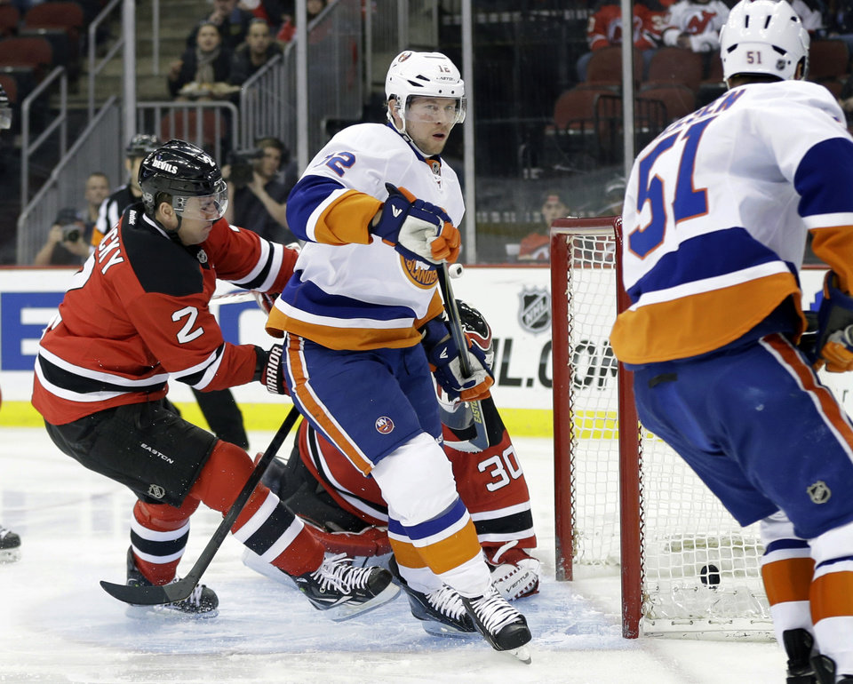 Photo - New York Islanders center Josh Bailey (12) scores a goal past New Jersey Devils' goalie Martin Brodeur (30) and Marek Zidlicky, of Czech Republic (2) during the first period of an NHL hockey game Monday, April 1, 2013, in Newark, N.J. (AP Photo/Mel Evans)