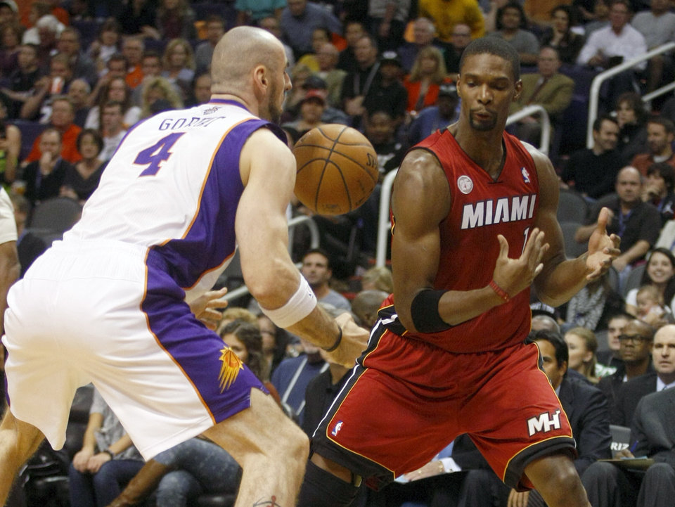 Miami Heat center Chris Bosh (1) loses the ball in front of Phoenix Suns center Marcin Gortat (4) in the first quarter during an NBA basketball game on Saturday, Nov. 17, 2012, in Phoenix. (Rick Scuteri/AP Photos)
