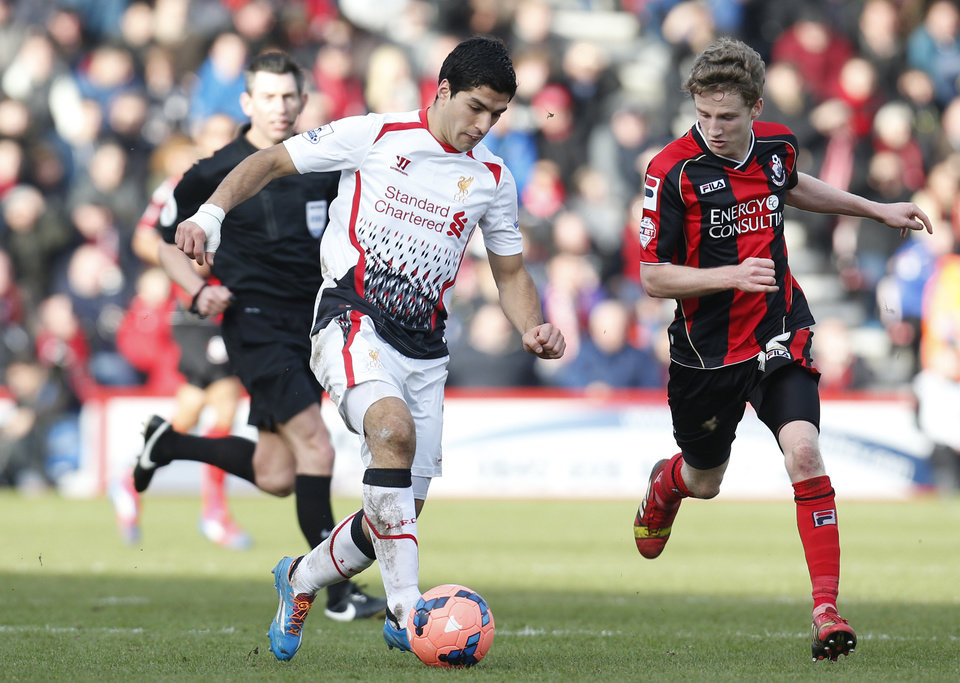 Photo - Liverpool's Luis Suarez, left, controls the ball past AFC Bournemouth's Eunan O'Kane, right, during their English FA Cup 4th round soccer match in Bournemouth, south England, Saturday, Jan. 25, 2014. Liverpool won the match 2-0.(AP Photo/Lefteris Pitarakis)