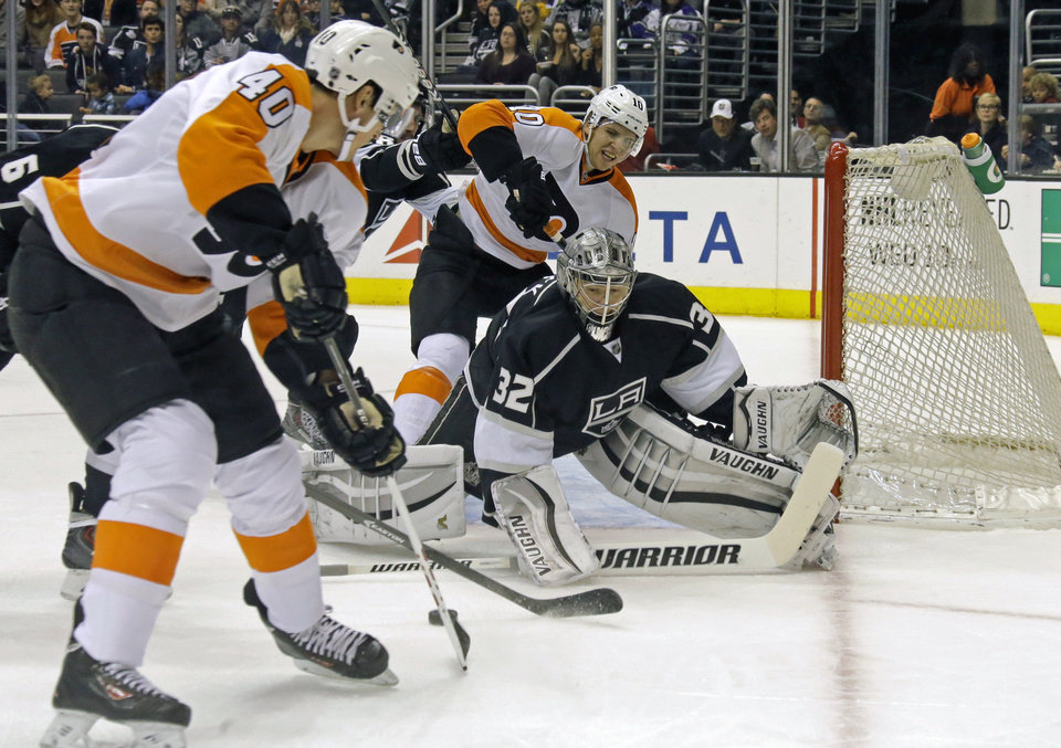 Photo - Los Angeles Kings goalie Jonathan Quick (32) defends as Philadelphia Flyers center Vincent Lecavalier (40) and center Brayden Schenn (10) approach in the first period of an NHL hockey game in Los Angeles Saturday, Feb. 1, 2014.  (AP Photo/Reed Saxon)
